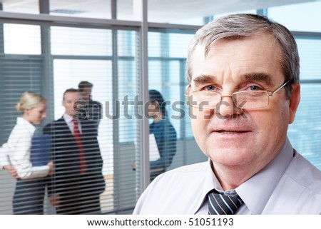 Portrait of mature boss in eyeglasses looking at camera in office - stock photo