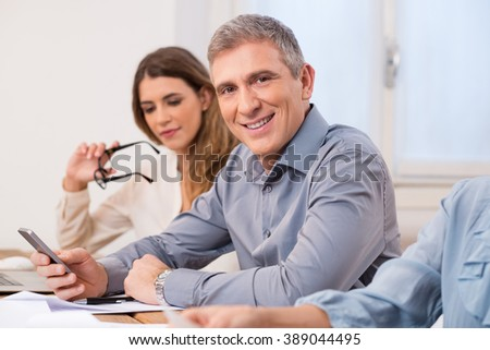 Portrait of mature business man looking at camera during a meeting. Senior man using mobile phone while looking at camera and smiling. Portrait of executive businessman with his colleaugues. - stock photo