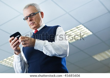 portrait of mature business man typing on mobile phone. Low angle view, Copy space - stock photo