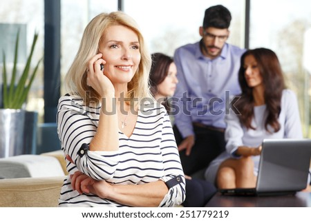 Portrait of mature business woman consulting at phone while colleagues sitting at background.  - stock photo