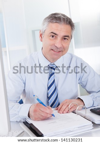Portrait Of Mature Businessman Calculating Finance At Office - stock photo