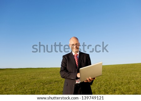 Portrait of mature businessman holding laptop on field against clear sky - stock photo