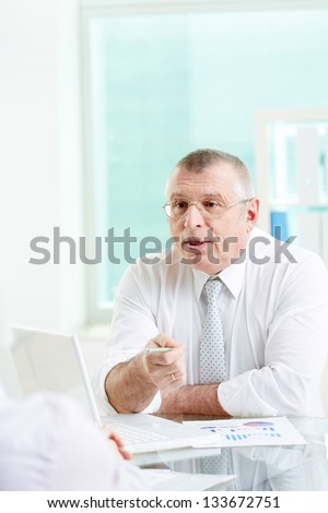 Portrait of mature businessman looking at his partner while pointing and talking to her in office - stock photo