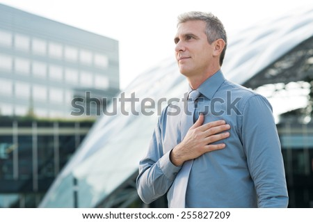 Portrait Of Mature Businessman Pledging With Hand On His Heart Outdoor - stock photo