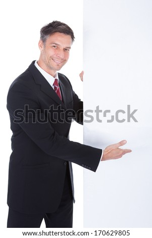 Portrait Of Mature Businessman Presenting Blank Placard
