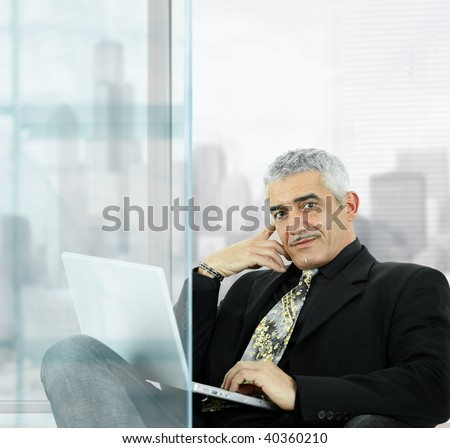 Portrait of mature businessman sitting  in front of windows in office, using laptop computer, smiling. - stock photo