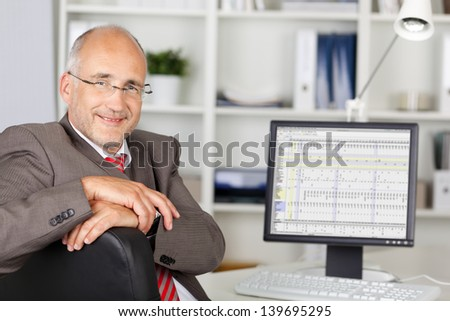 Portrait of mature businessman smiling with computer on desk in office - stock photo