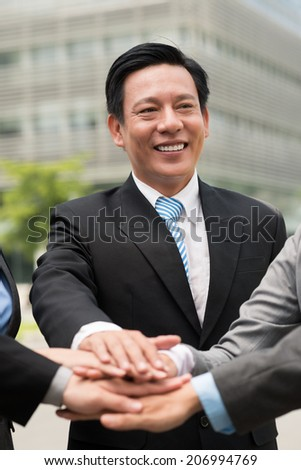 Portrait of mature businessman stacking hands with his colleagues - stock photo