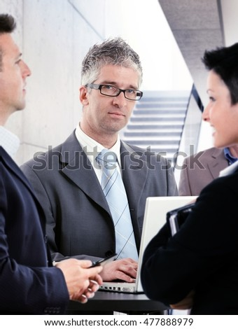 Portrait of mature businessman talking to colleagues.