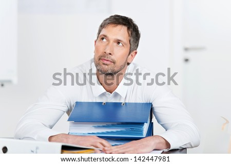 Portrait of mature businessman with binders at desk in office - stock photo