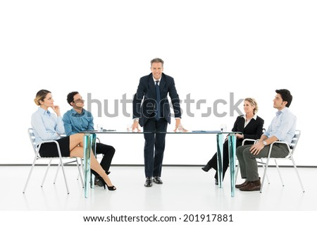 Portrait Of Mature Businessman With His Colleague In Business Meeting Against Projection Screen - stock photo