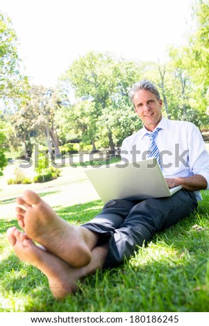Portrait of mature businessman with laptop sitting on grass in park