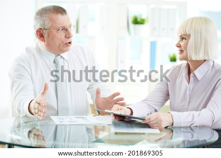 Portrait of mature businesswoman listening attentively to her boss explanations at meeting - stock photo