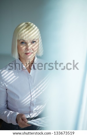 Portrait of mature businesswoman looking at camera in office - stock photo