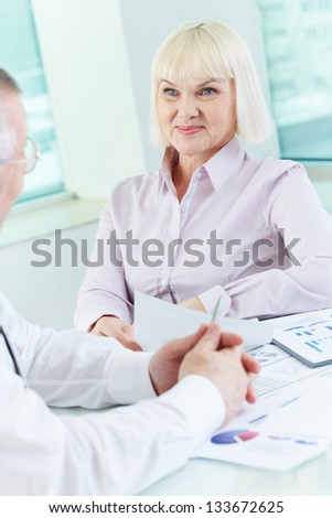 Portrait of mature businesswoman looking at her partner while talking to him at workplace - stock photo