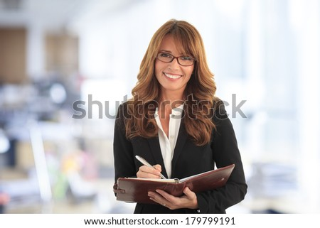 Portrait of mature businesswoman standing and making a list in her office. - stock photo