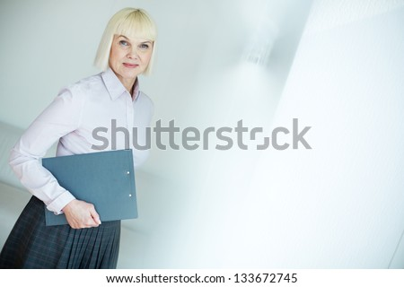 Portrait of mature businesswoman with clipboard looking at camera in office - stock photo