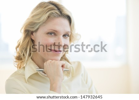 Portrait of mature businesswoman with hand on chin smiling in office - stock photo