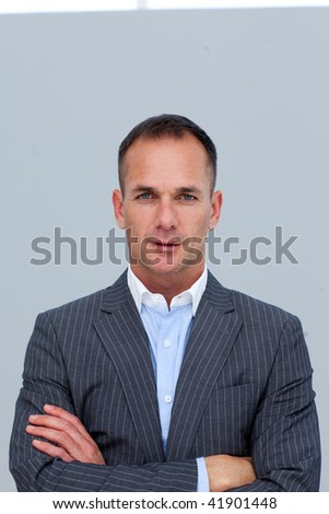 Portrait of mature confident businessman with folded arms - stock photo
