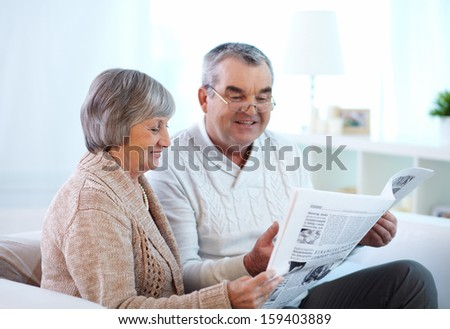 Portrait of mature couple reading newspaper together - stock photo