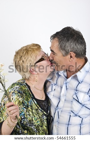 Portrait of mature couple 50s kissing in front of image,woman holding  flowers