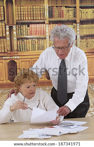 Portrait of mature Couple Sitting in reading room  looking at  bills  - stock photo