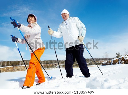Portrait of mature couple skiing outside - stock photo
