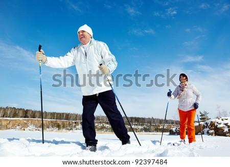 Portrait of mature couple skiing outside - stock photo
