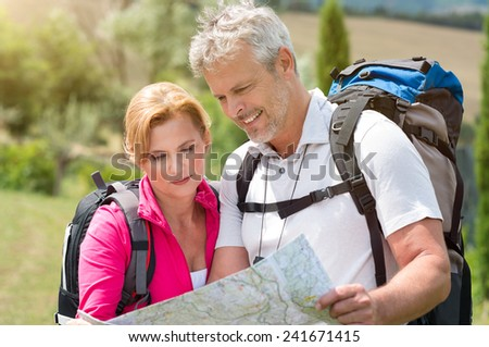 Portrait Of Mature Couple With Backpack Looking At Map - stock photo