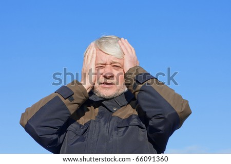 Portrait of mature desperate man with grey hair on blue sky of the background. - stock photo