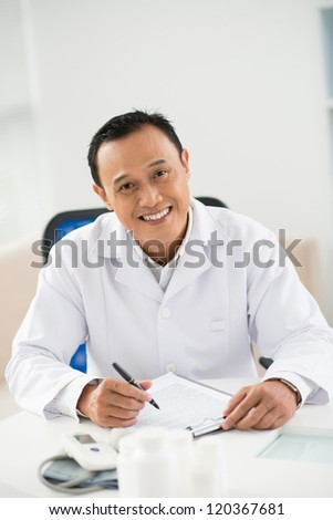 Portrait of mature doctor sitting in his office and looking at camera - stock photo