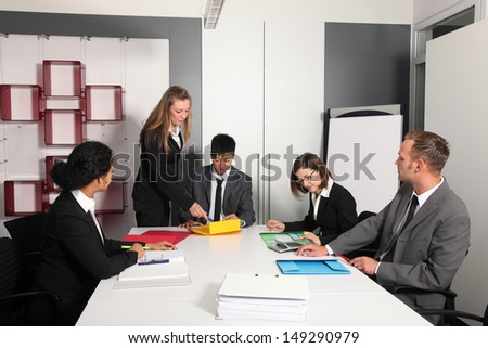 Portrait of mature female executive discussing with male associates in office