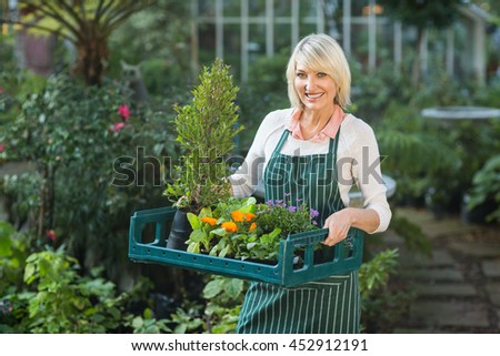 Portrait of mature female gardener carrying plants in crate outside greenhouse