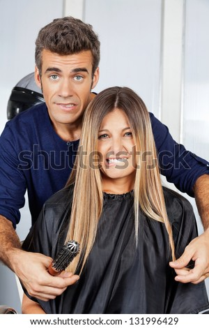 Portrait of mature hair dresser and client making faces at salon - stock photo