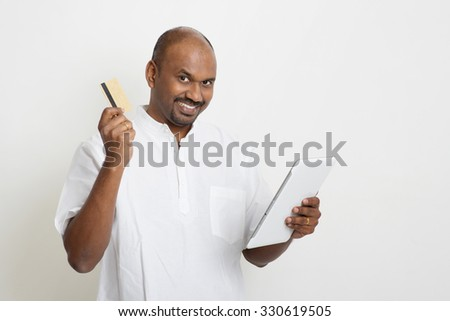 Portrait of mature Indian man shopping online using tablet pc, making payment by credit card. Asian man standing on plain background with shadow and copy space.  - stock photo