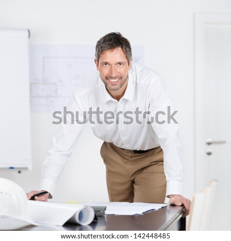 Portrait of mature male architect with blueprints at desk in office - stock photo