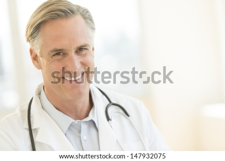 Portrait of mature male doctor with stethoscope around neck smiling in hospital