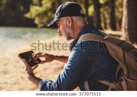 Portrait of mature male hiker using digital tablet outdoors. Senior man with backpack sitting by a lake looking at his digital tab for directions and location. - stock photo