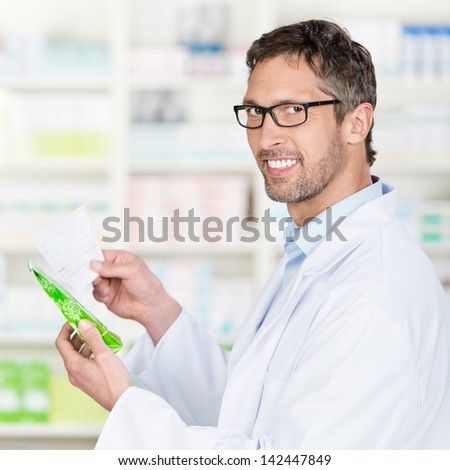 Portrait of mature male pharmacist holding prescription paper and product in pharmacy - stock photo