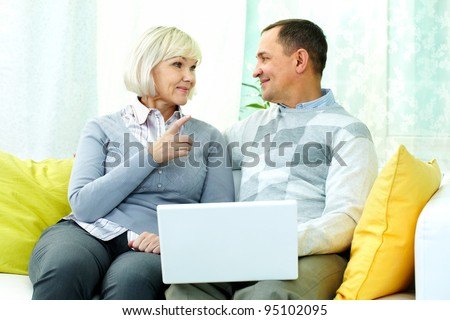 Portrait of mature man and his wife chatting at home during computer work - stock photo