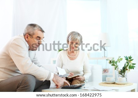 Portrait of mature man and his wife making financial revision at home - stock photo