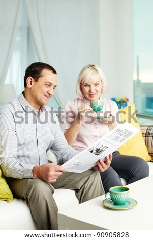 Portrait of mature man and his wife reading newspaper in the morning at home - stock photo