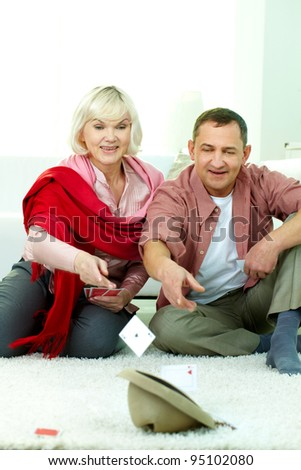 Portrait of mature man and his wife throwing cards into hat at home - stock photo