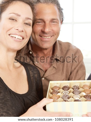 Portrait of mature man and woman with a box of luxury chocolates.