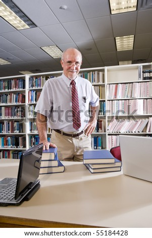 Portrait of mature man at library table with textbooks, professor researching - stock photo