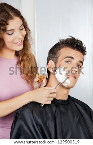 Portrait of mature man getting a shave from female barber at salon - stock photo