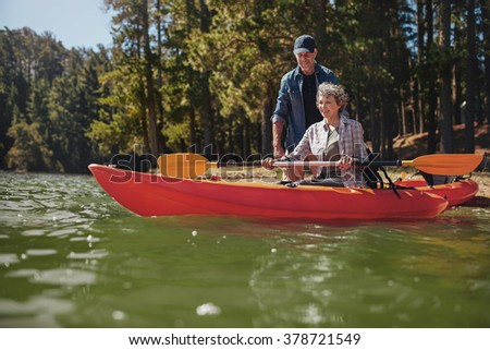 Portrait of mature man giving instruction to woman paddling a kayak in the lake. Senior woman getting kayaking lessons from a man. - stock photo