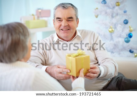 Portrait of mature man giving present to his wife - stock photo