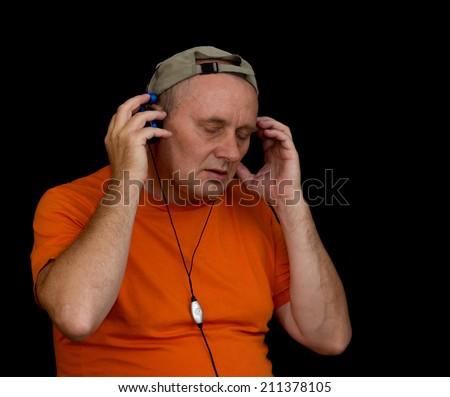 Portrait of mature man listening music with headphones - stock photo