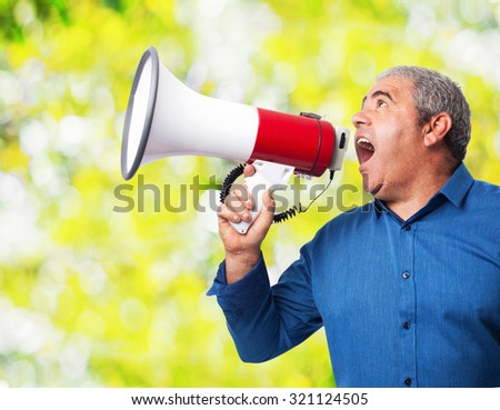 portrait of mature man shouting with the megaphone